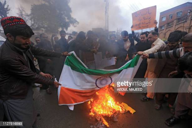 Pakistani protesters burn an Indian national flag during a protest in Peshawar on February 26 following the Indian Air Force strike launched on a...