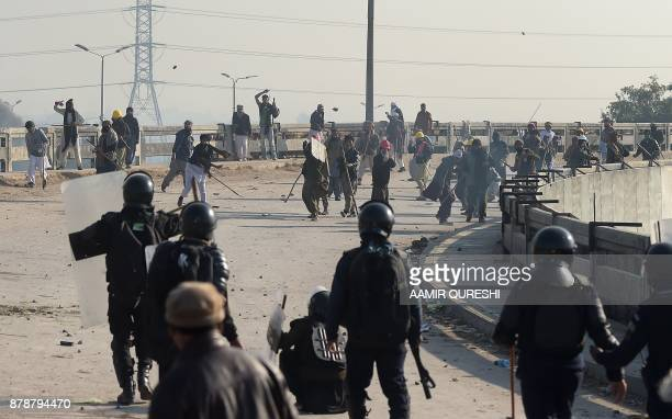 TOPSHOT Pakistani protesters from the TehreekiLabaik Yah Rasool Allah Pakistan religious group throw rocks toward riot policemen during a clash in...