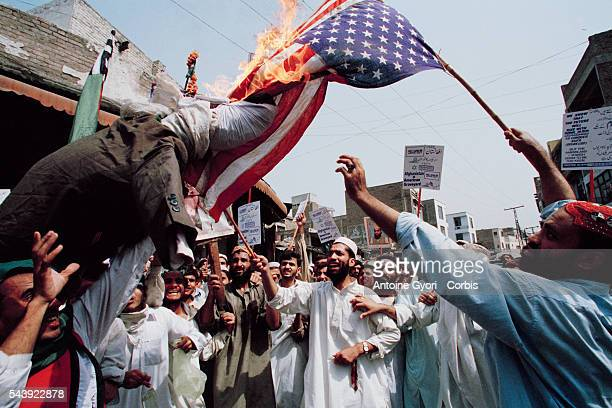Pakistani protesters in support of the Taliban regime and Osama bin Laden burn an American flag in Peshawar