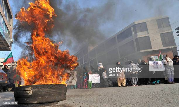 Pakistani protesters march alongside a burning tyre in a protest against the killing of the Shiite Muslims in Lahore on February 6 2009 Pakistani...