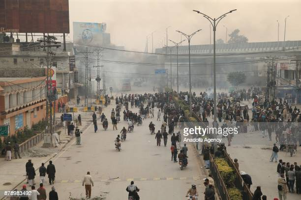 Pakistani protesters throw stones at security forces after they launched a crackdown on Saturday morning against protesters who had been blocking the...