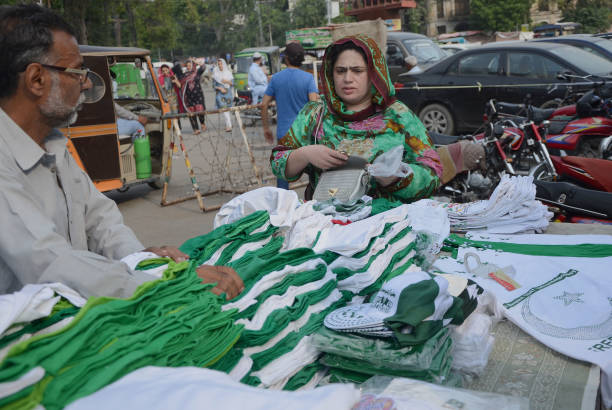 Pakistani purchasing national flags buntings and other stuff displayed in a local market as the nation starts preparing for the 70th Independence Day.