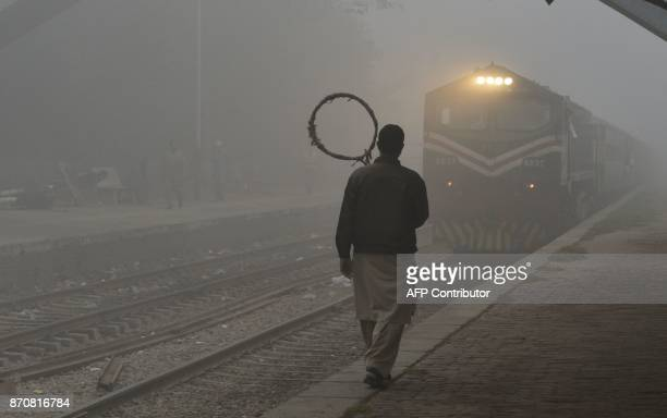 A Pakistani railway worker walks on the platform while a train arrives at a station in heavy smog in Lahore on November 6 2017 / AFP PHOTO / ARIF ALI