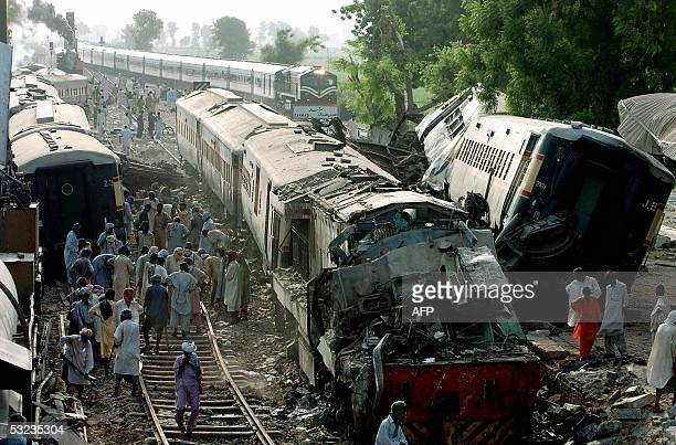 Pakistani railway workers clear debris from the track at the crash scene in Ghotki some 430 kilometres northeast of Karachi 14 July 2005 Relatives...
