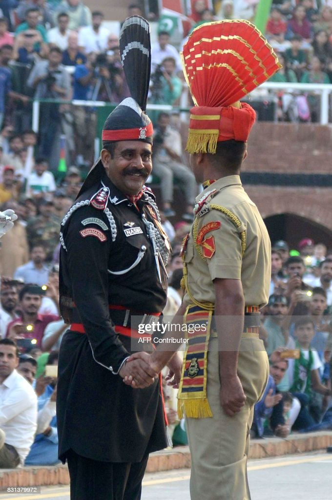 A Pakistani Ranger and Indian Border Security Force official shake hands during the daily beating of the retreat ceremony at the IndiaPakistan Wagah..