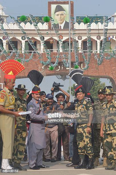 Pakistani Ranger sector Commander Shaukat Ali presents sweets to Indian Border Security Force Commandant Sudeep during a ceremony to celebrate...