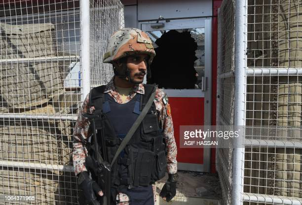 A Pakistani ranger stands in front of a damaged gate at the Chinese consulate after an attack in Karachi on November 23 2018 At least two policemen...