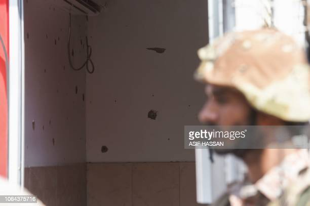 A Pakistani ranger stands in front of a gate next to bullet holes outside the Chinese consulate after an attack in Karachi on November 23 2018 At...