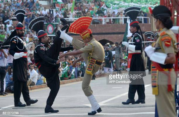 TOPSHOT Pakistani Rangers and Indian Border Security Force personnel perform perform during the daily beating of the retreat ceremony at the...