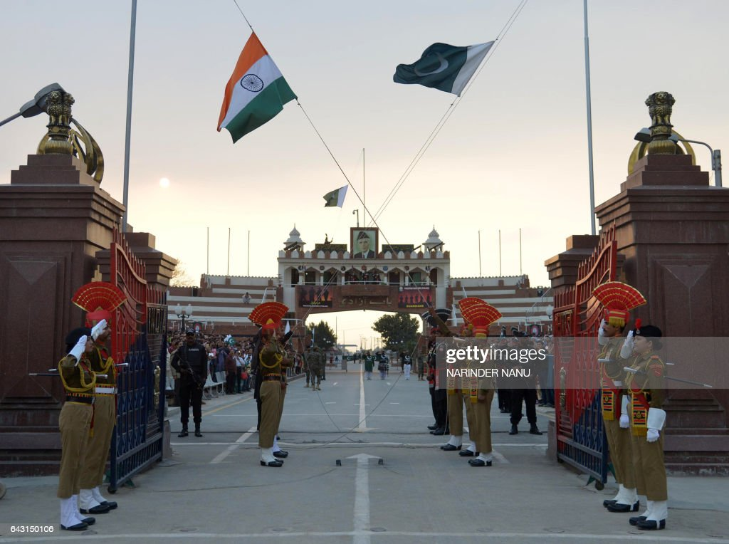 Pakistani Rangers and Indian Border Security Force personnel salute their national flags as they perform during the daily beating of the retreat...