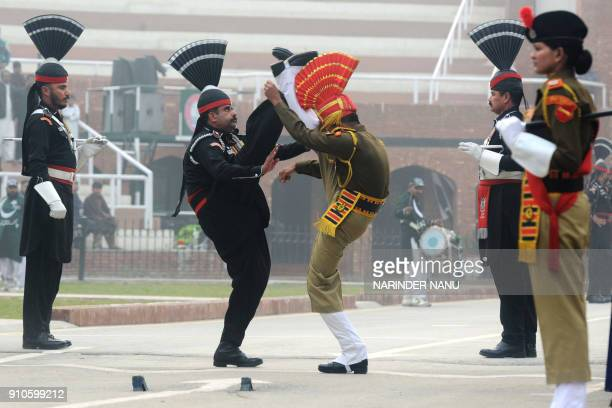 Pakistani Rangers and Indian Border Security Force personnel take part in the daily beating of the retreat ceremony during India's 69th Republic Day...