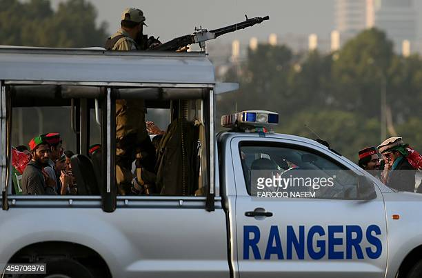 Pakistani Rangers security vehicle drives past Pakistan Tehreek-e-Insaf supporters as they gather to join a sit-in protest against the government...