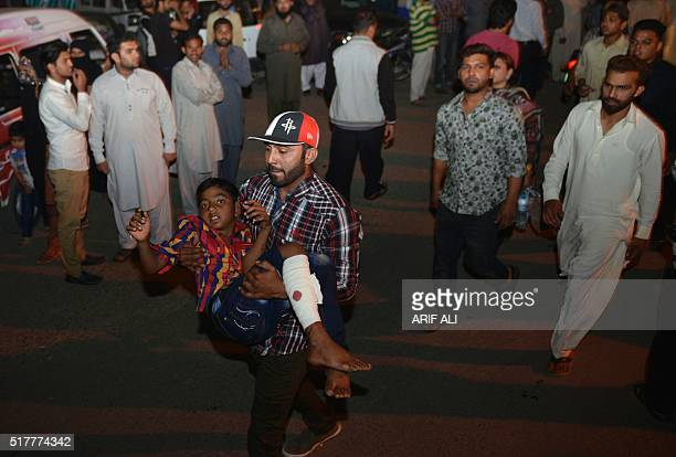 A Pakistani relative carries an injured child to the hospital in Lahore on March 27 after at least 56 people were killed and more than 200 injured...