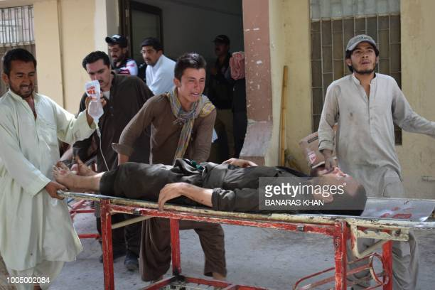 Pakistani relative reacts as he pushes an injured blast victim on a stretcher at a hospital after a suicide attack near a polling station in Quetta...