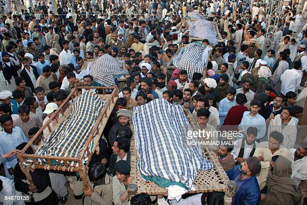 Pakistani relatives and residents carry the remains of suicide attack victims during their funeral in Dera Ghazi Khan on February 6 2009 Police said...