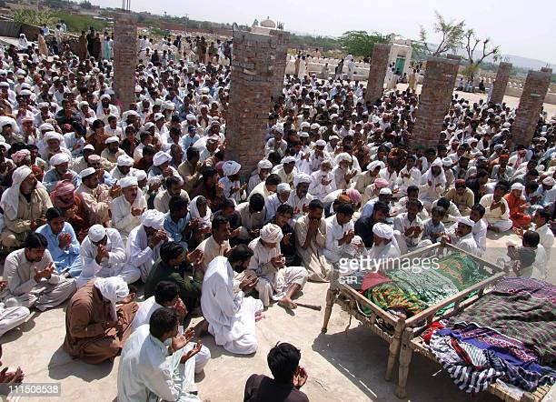 Pakistani relatives and residents offer prayers for the blast victims of pilgrims during the funeral ceremony in Dera Ghazi Khan on April 4 2011 The...