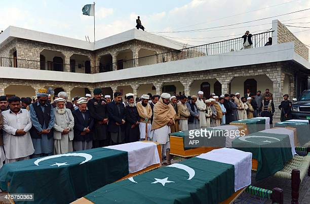 Pakistani relatives and security officials offer funeral prayers for paramilitary soldiers who were killed in roadside bomb attacks in the Lashora...