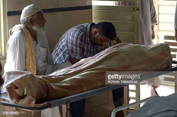 Pakistani relatives gather beside the bodies of heatstroke victims outside the cold storage of the Edhi morgue in Karachi on June 23 2015 The death...