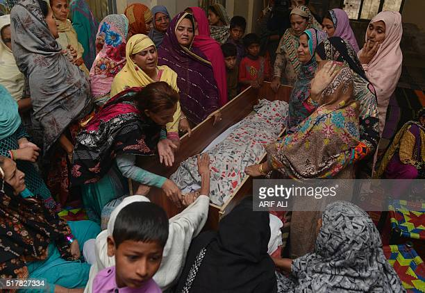 Pakistani relatives mourn over the body of a victim during a funeral following an overnight suicide bombing in Lahore on March 28 2016 The toll from...