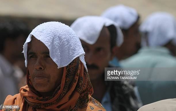 Pakistani relatives of heatstroke victims their heads covered with wet towels wait outside a hospital during a heatwave in Karachi on June 29 2015...