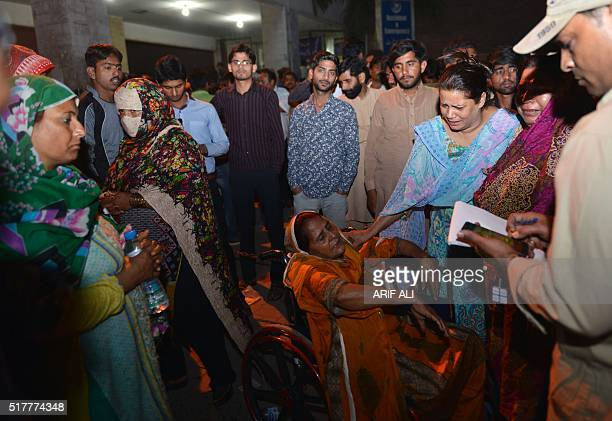 Pakistani relatives of injured victims gather outside the hospital in Lahore on March 27 after at least 56 people were killed and more than 200...