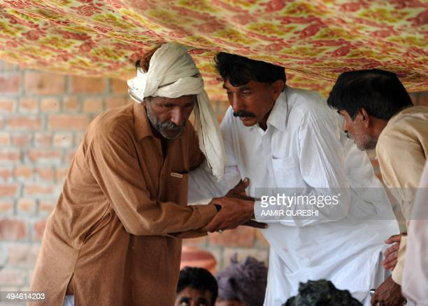 Pakistani relatives of Mohammad Iqbal offer him their condolences as they pray for his wife Farzana Parveen who was beaten to death with bricks by...
