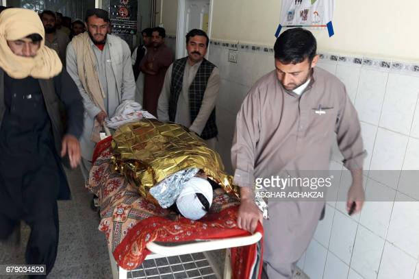 Pakistani relatives push a stretcher carrying the body of a victim at a hospital following cross border firing in the border town of Chaman on May 5...