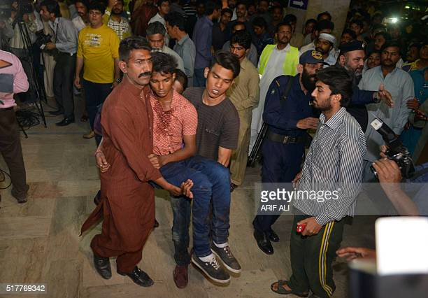Pakistani relatives shift an injured bomb blast victim into a hospital after a bomb blast in Lahore on March 27 2016 At least 25 people were killed...