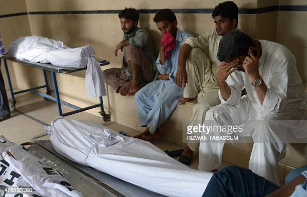 Pakistani relatives sit beside the bodies of heatstroke victims outside the cold storage of the Edhi morgue in Karachi on June 23 2015 The death toll...