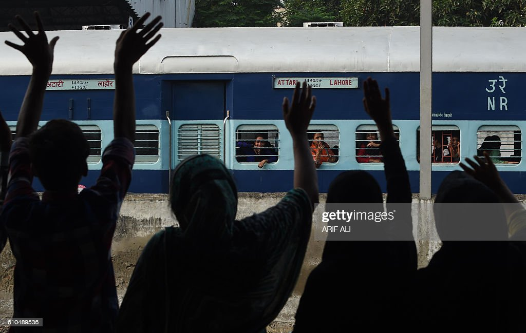 TOPSHOT Pakistani relatives wave towards Indian travelers as they leave on the Indiabound Samjhota Express from Lahore Railway Station in Lahore on...