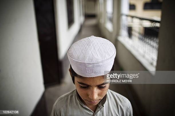 Pakistani religious student Ilyass poses in the corridor of the dormitory at an Islamic seminary in Rawalpindi on June 29, 2010. According to...