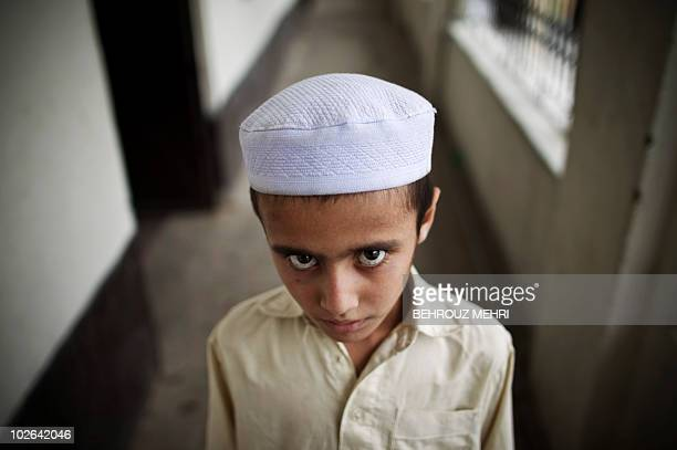 Pakistani religious student Loghman poses in the corridor of the dormitory at an Islamic seminary in Rawalpindi on June 29, 2010. According to...