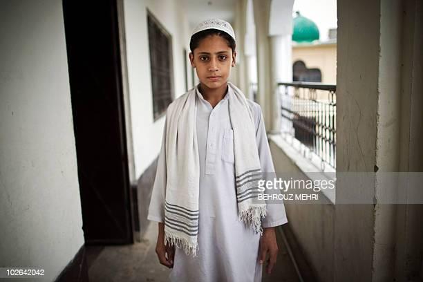 Pakistani religious student Muhibbullah poses in the corridor of the dormitory at an Islamic seminary in Rawalpindi on June 29, 2010. According to...