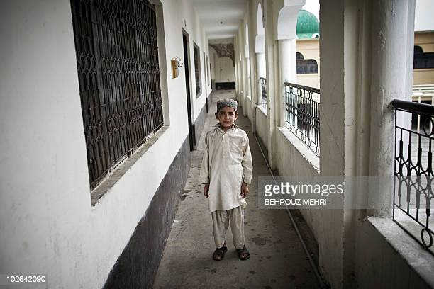 Pakistani religious student Yassir poses in the corridor of the dormitory at an Islamic seminary in Rawalpindi on June 29, 2010. According to...