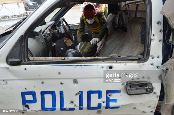 A Pakistani rescue services official searches a police vehicle after a bomb attack in Sir Dheri some 30 kilometres north of the main northwestern...