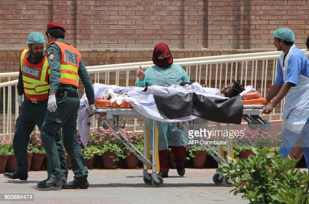 Pakistani rescue workers and paramedics bring a burns victim injured after an oil tanker caught fire following an accident on a highway in central...
