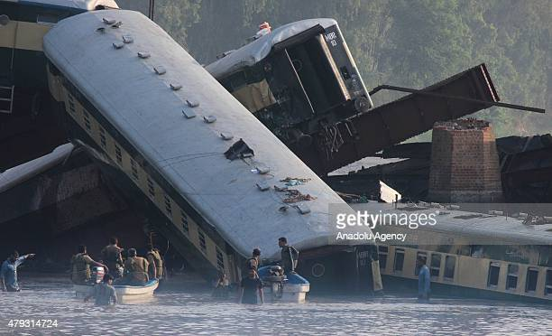 Pakistani rescue workers and troops inspect the wreckage of a train after it derailed into a canal in Wazirabad in the Punjab province on July 3 2015...
