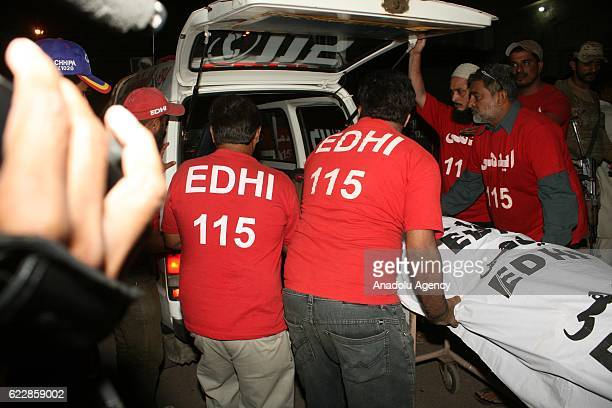 Pakistani rescue workers and volunteers unload victims of bomb blast from an ambulance upon his arrival at a local hospital in Hub town near Karachi...