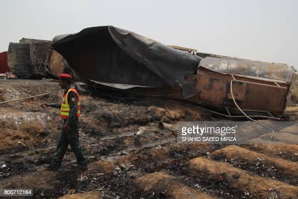 Pakistani rescue workers gather beside an oil tanker which caught fire following an accident on a highway near the town of Ahmedpur East some 670...