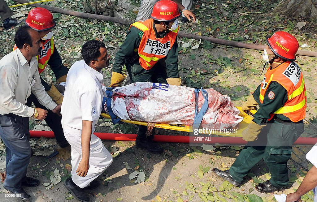 Pakistani rescue workers remove a dead body from the parking