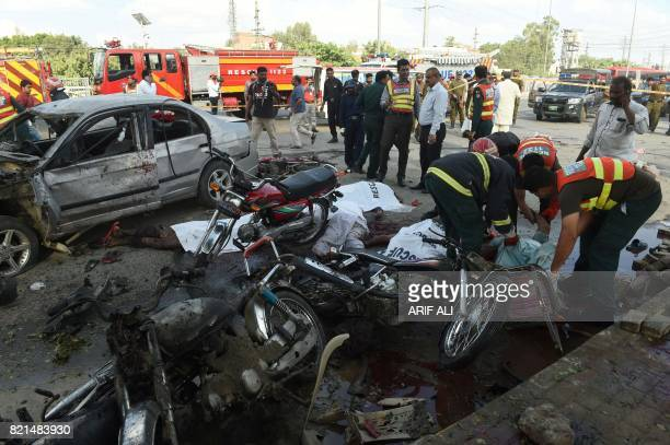 TOPSHOT Pakistani rescue workers try to move the bodies of victims at the site of an explosion in Lahore on July 24 2017 An explosion killed at least...
