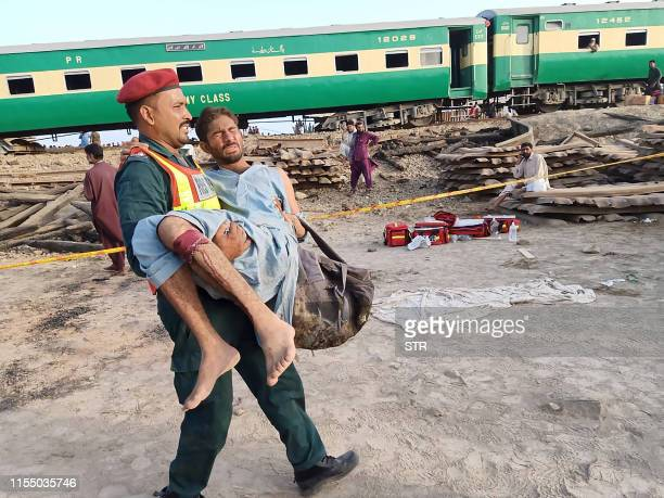 Pakistani rescuer carries an injured passenger at the site of train accident in Rahim Yar Khan district in Punjab province on July 11 2019 t least...
