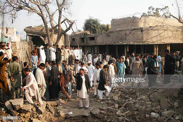 Pakistani rescuers and onlookers gather at the site of a car bomb blast in Dera Ghazi Khan on December 15 2009 A powerful car bomb exploded in a busy...