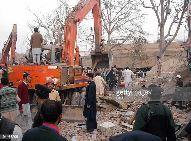 Pakistani rescuers and onlookers work at the site of a car bomb blast in Dera Ghazi Khan on December 15 2009 A powerful car bomb exploded in a busy...