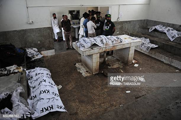Pakistani rescuers are pictured at a morgue with the bodies of airport workers who were found inside the premises of a coldstorage cargo facility at...