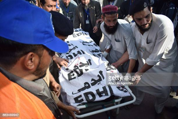 Pakistani rescuers carry a body on a stretcher at a hospital following an attack on Peshawar Agricultural Training Institute by Taliban militants in...