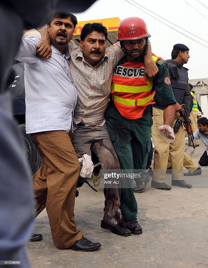 Pakistani rescuers help an injured worshiper at one of two mosques stormed by gunmen in Lahore on May 28, 2010. Gunmen dressed in suicide vests stormed two Pakistani mosques belonging to a minority sect in Lahore on May 28, killing at least 56 people and reducing prayers to a bloodbath, officials said. In one of the deadliest attacks in Pakistan's second city, which has been increasingly hit by Taliban and Al-Qaeda-linked violence, squads of militants stormed into prayer halls, firing off guns and grenades, and taking hostages.