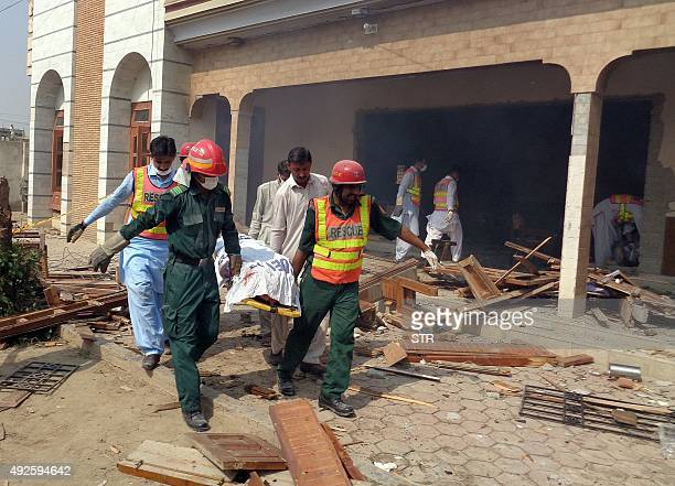 Pakistani rescuers move the body of a blast victim at the site of a suspected suicide bomb attack in Taunsa town near Dera Ghazi Khan city in the...