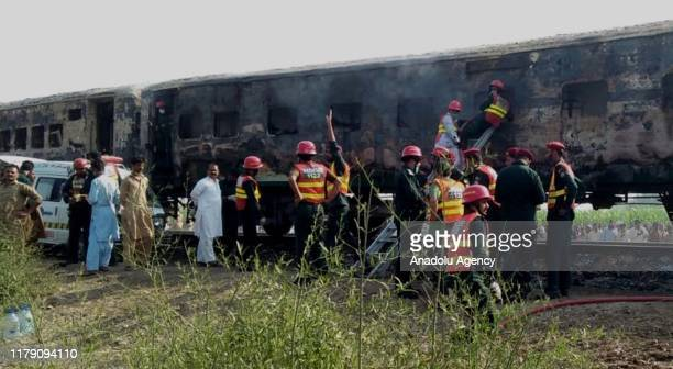 Pakistani rescuers search for victims in a train as fire erupted in it in a gas cylinder blast at Chani Goth area in Rahimyar District in southern...