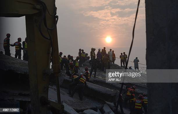 Pakistani rescuers search for victims in the rubble of a collapsed factory on the outskirts of Lahore on November 7 2015 Rescuers in Pakistan have...